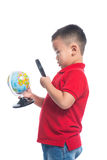 Portrait asian child holding earth globe map in his hand. Looking through magnifying loupe Stock Images