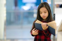 Portrait Asian child holding open textbook in hands in book store stock photo
