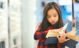 Portrait Asian child holding open textbook in hands in book store stock photos