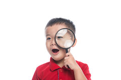 Portrait asian child looking through magnifying loupe Stock Photo