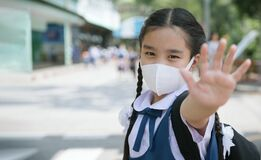 Portrait Asian children girl wear mask to protect PM 2.5 dust and air pollution. Portrait of Thai student wearing protection mask
