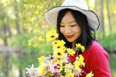 Happy Asian Chinese woman beauty girl smile hold a bunch of flower walk by lake in forest spring park sit on bench enjoy cozy life royalty free stock images
