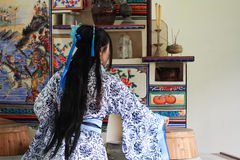 Portrait of Asian Chinese girl in traditional dress, wear blue and white porcelain style Hanfu, do housework in a ancient kitchen. Asian Chinese girl in Royalty Free Stock Images