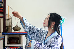Portrait of Asian Chinese girl in traditional dress, wear blue and white porcelain style Hanfu, Light the candles on the stove Royalty Free Stock Images