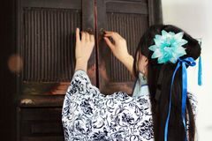 Portrait of Asian Chinese girl in traditional dress, wear blue and white porcelain style Hanfu, open ancient cupboard. Asian Chinese girl in traditional dress Stock Images