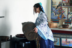 Portrait of Asian Chinese girl in traditional dress, wear blue and white porcelain style Hanfu, Pour water into a vat. Asian Chinese girl in traditional dress Royalty Free Stock Photo