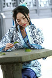 Portrait of Asian Chinese girl in traditional dress, wear blue and white porcelain style Hanfu, sit on a stone chair. Asian Chinese girl in traditional dress Stock Photo