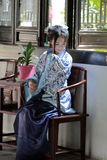 Portrait of Asian Chinese girl in traditional dress, wear blue and white porcelain style Hanfu, sit on a wooden chair. Asian Chinese girl in traditional dress Stock Image