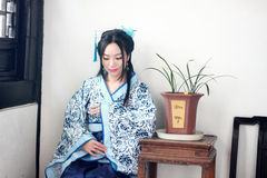Portrait of Asian Chinese girl in traditional dress, wear blue and white porcelain style Hanfu, Sitting elegant on a wooden chair. Asian Chinese girl in Stock Photos
