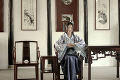 Portrait of Asian Chinese girl in traditional dress, wear blue and white porcelain style Hanfu, Sitting elegant on a wooden chair. Asian Chinese girl in Royalty Free Stock Images