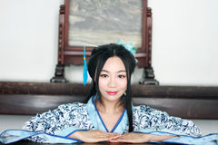 Portrait of Asian Chinese girl in traditional dress, wear blue and white porcelain style Hanfu, Sitting elegant on a wooden chair. Asian Chinese girl in Stock Photo
