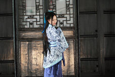 Portrait of Asian Chinese girl in traditional dress, wear blue and white porcelain style Hanfu, stand by a door Stock Photo