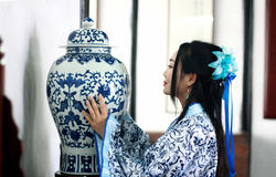 Portrait of Asian Chinese girl in traditional dress, wear blue and white porcelain style Hanfu, Standing at the table looking at t. Asian Chinese girl in Royalty Free Stock Image