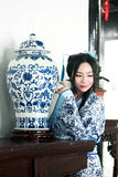 Portrait of Asian Chinese girl in traditional dress, wear blue and white porcelain style Hanfu, Standing at the table looking at t. Asian Chinese girl in Stock Photo