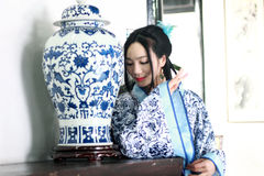 Portrait of Asian Chinese girl in traditional dress, wear blue and white porcelain style Hanfu, Standing at the table looking at t. Asian Chinese girl in Royalty Free Stock Photos