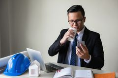 Businessman drink coffee and play smartphone. Portrait of Asian civil engineer happy manager drink hot coffee, play social media, shopping onlinem and check royalty free stock photos