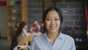 Portrait of asian confident businesswoman looking at camera and smiling while her multi-ethnic team working on start-up