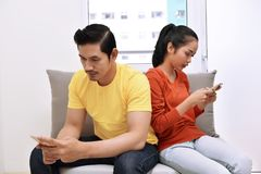 Portrait of asian couple busy with their mobile phones in their Stock Image