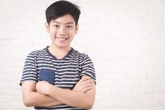 Portrait of asian cute boy and good looking. Portrait of asian cute boy and good looking with smile on white brick wall background stock images