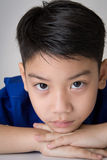 Portrait of asian cute boy sad and  looking very disappointed. On gray background Royalty Free Stock Photography
