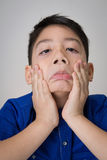 Portrait of asian cute boy sad and  looking very disappointed. On gray background Stock Photo