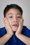 Portrait of asian cute boy sad and  looking very disappointed. On gray background Stock Photos