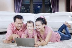Asian family plays laptop in the apartment. Portrait of Asian family playing a laptop while enjoying leisure time together in the apartment Stock Image