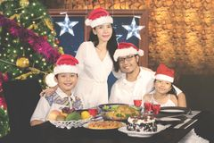 Asian family at Christmas dinner. Portrait of Asian family smiling at the camera while having Christmas dinner in the kitchen Royalty Free Stock Images
