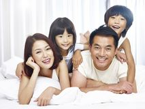Portrait of asian family with two children. Happy asian family with two children having fun in bed at home stock photos