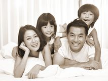 Portrait of asian family with two children. Happy asian family with two children having fun in bed at home, black and white sepia toned stock images