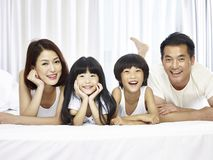 Portrait of asian family with two children. Happy asian family with two children lying on front in bed looking at camera smiling royalty free stock image