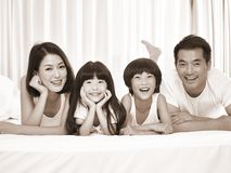 Portrait of asian family with two children. Happy asian family with two children lying on front in bed looking at camera smiling, black and white sepia royalty free stock photography