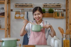 Asian female cooking food in kitchen stock image