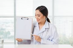 Portrait of asian female doctor pointing on clipboard while sitt. Ing at consulting room Royalty Free Stock Photography