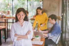 Portrait of asian female leader of working team coworking office ,Smiling of happy chinese girl in modern office royalty free stock photography