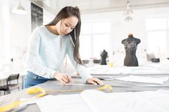 Asian Tailor in Atelier. Portrait of Asian female tailor tracing fabric with white chalk while sewing custom made clothes in modern atelier workshop, copy space royalty free stock photography