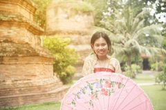 Portrait of Asian female in traditional dresses pose a holding umbrella. Asian woman in traditional dresses holding umbrella near Pagoda in Wat Yai Chai Monkol stock photo