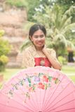 Portrait of Asian female in traditional dresses pose a holding umbrella. Asian woman in traditional dresses holding umbrella near Pagoda in Wat Yai Chai Monkol stock photos