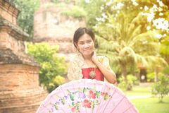 Portrait of Asian female in traditional dresses pose a holding umbrella. Asian woman in traditional dresses holding umbrella near Pagoda in Wat Yai Chai Monkol stock photography