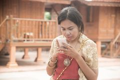Portrait of Asian female in traditional dresses pose use mobile. stock photos