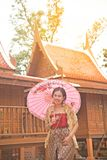 Portrait of Asian female in traditional dresses pose at Thai home. Portrait of Asian female in traditional dresses pose a holding umbrella at Thai home stock photos