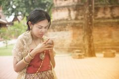 Portrait of Asian female in traditional dresses pose use mobile. Portrait of Asian female in traditional dresses pose a holding use mobile at ancient Thai royalty free stock photo