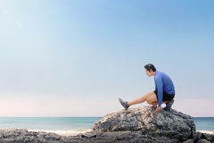 Portrait of asian fitness man stretching legs before jogging Stock Photography