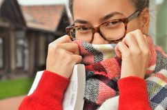 Portrait of an Asian girl in glasses, she screwed her face with a scarf. Only her eyes and hands are visible. The hair is tied to the knot. Standing on the Royalty Free Stock Photography