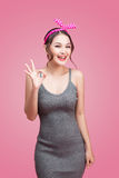 Portrait of asian girl with pretty smile in pinup style with han. Ds gesture on pink background Royalty Free Stock Image