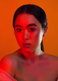 Portrait of an Asian girl with red eyebrows and make-up on a yellow background with red light Royalty Free Stock Photography