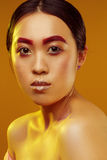 Portrait of an Asian girl with red eyebrows and make-up on a yellow background with yellow light Stock Image