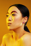 Portrait of an Asian girl with red eyebrows and make-up on a yellow background with yellow light Royalty Free Stock Photography