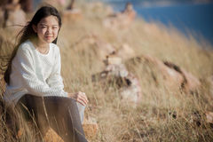 Portrait of asian girl relaxing emotion sitting in grass field a Royalty Free Stock Images