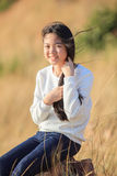 Portrait of asian girl relaxing emotion sitting in grass field a Stock Images